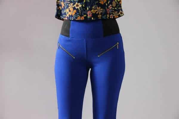 Close up of a person wearing blue jeggings with stylish side zippers and a floral shirt
