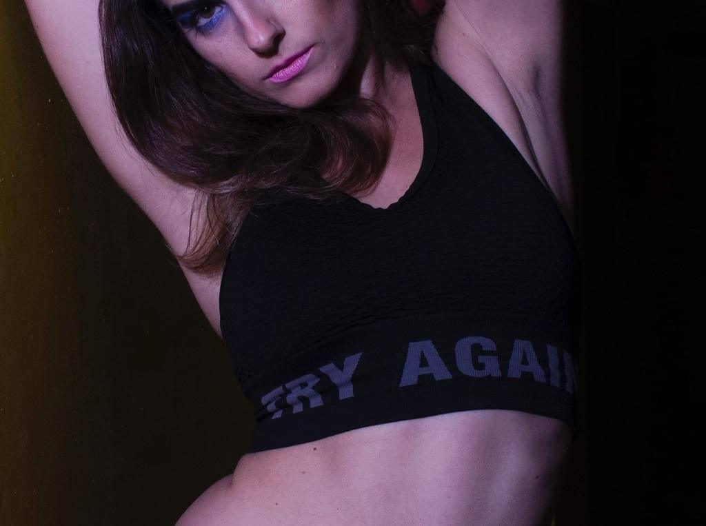 """Woman wearing a black sports bra with the text """"try again"""""""