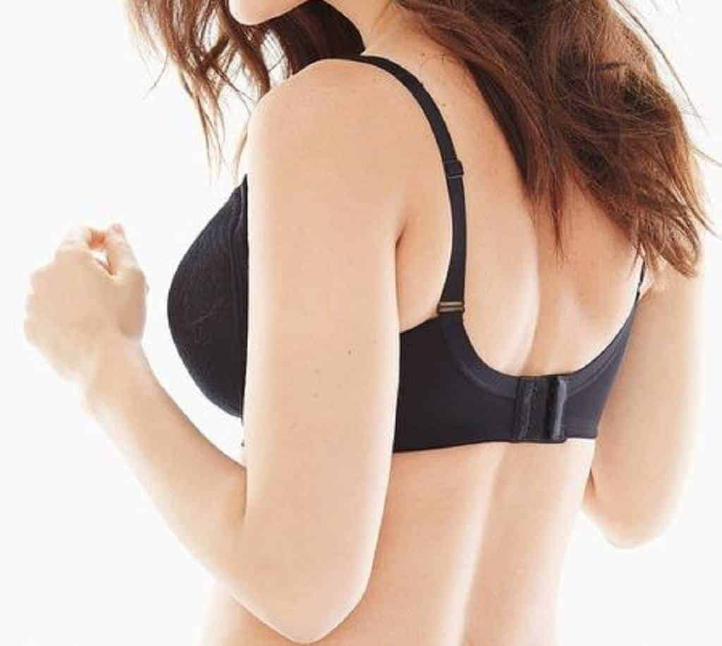 Woman with dark hair is wearing a black full coverage bra with her back turned to the camera