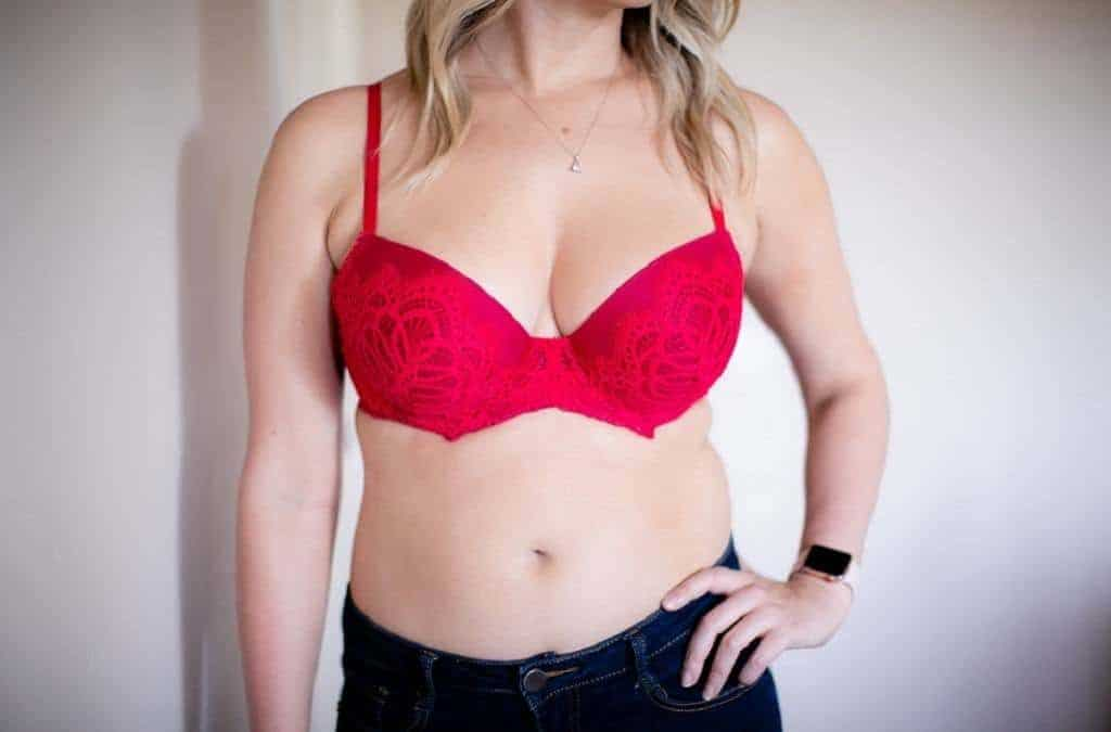 Blonde haired woman wears a red lce full coverage bra and some dark blue jeans