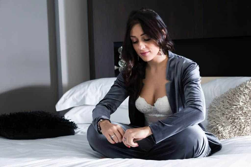 A woman sitting on a bed wearing silk pajamas showing her white underwire bra