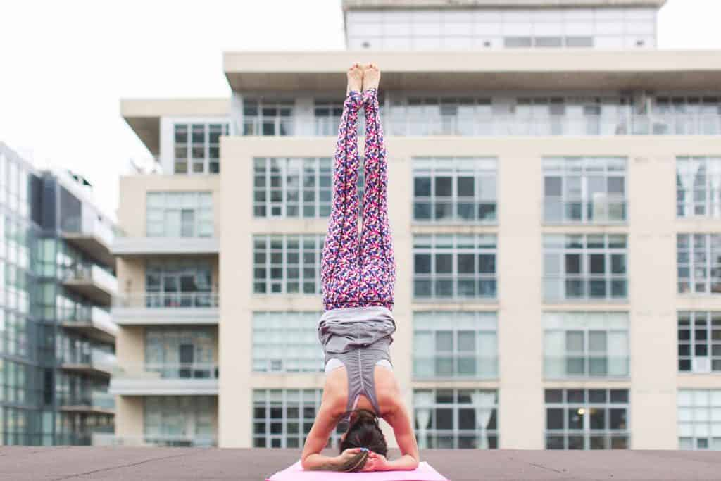 Woman wearing pink yoga pants doing a handstand