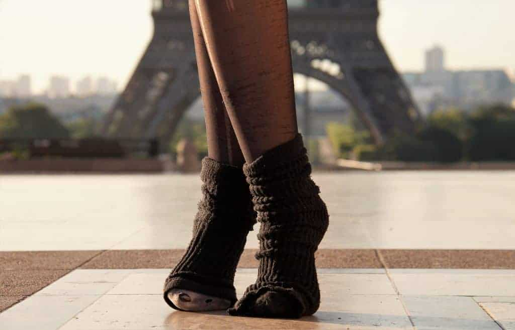 Girl wearing black socks poses in front of the eiffel tower