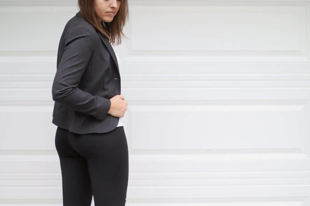 A woman wearing black leggings and a suit jacket