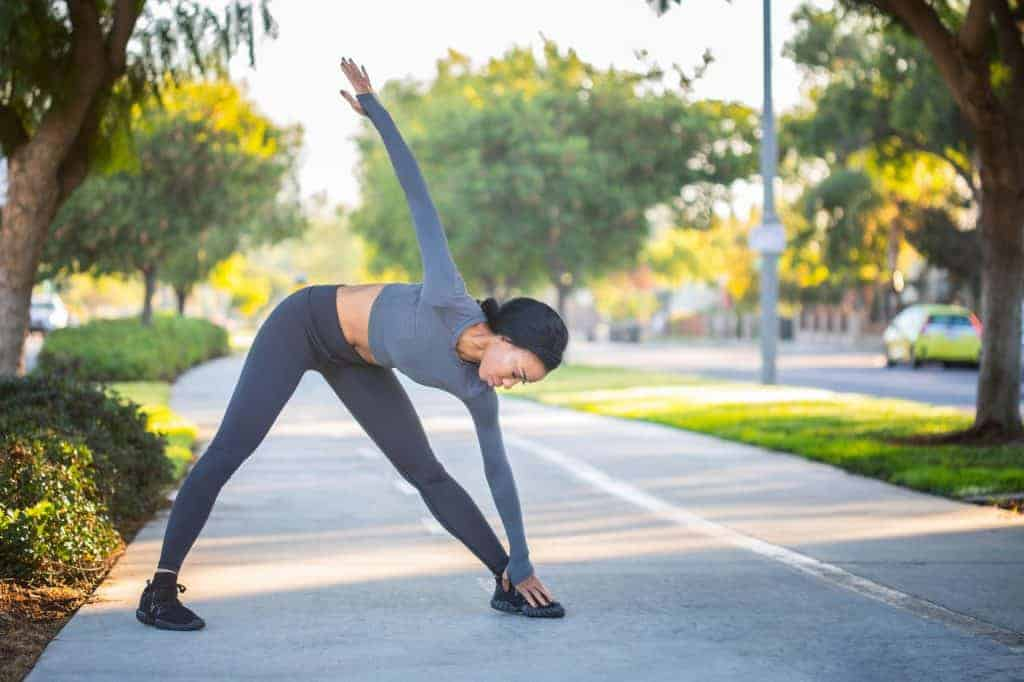 Woman stretching her arms down to the ground wearing leggings that makes her butt look bigger