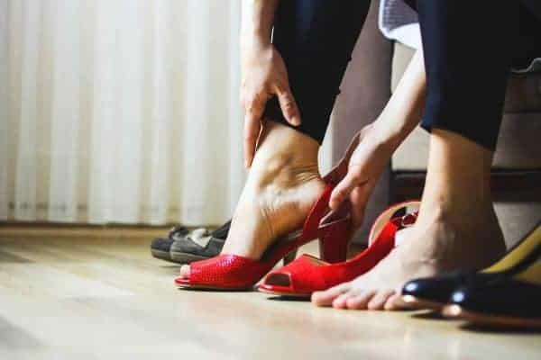 Woman wearing black leggings putting on a pair of red heels