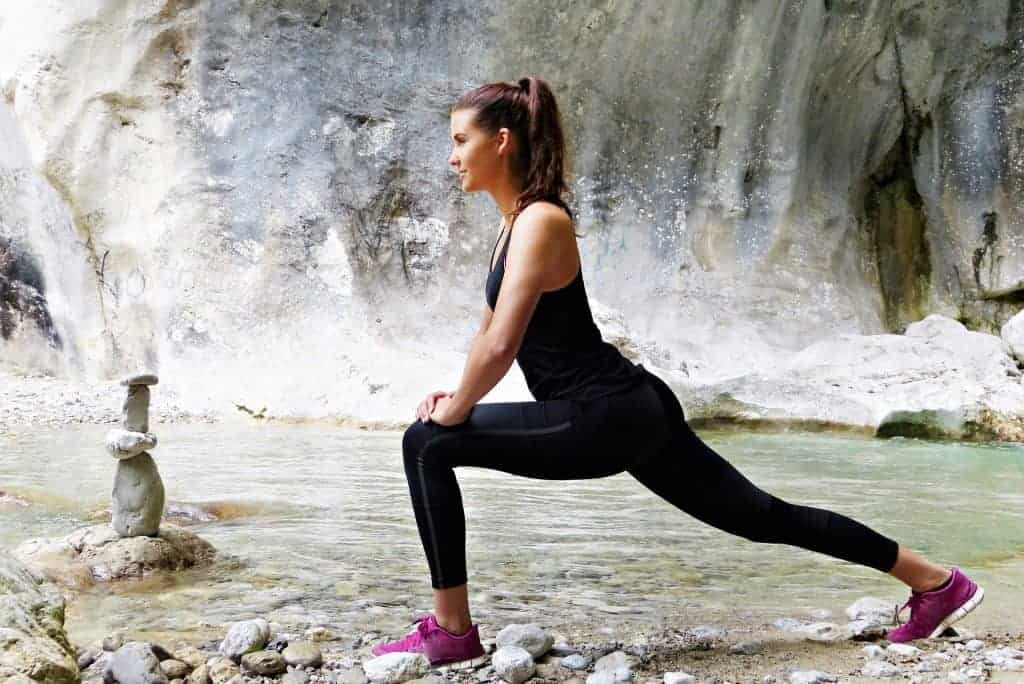 Young woman in leggings doing stretches outdoors