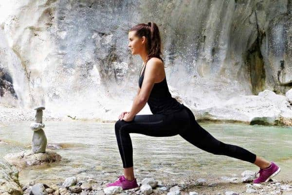 Woman doing outdoor yoga while wearing a black top and black leggings