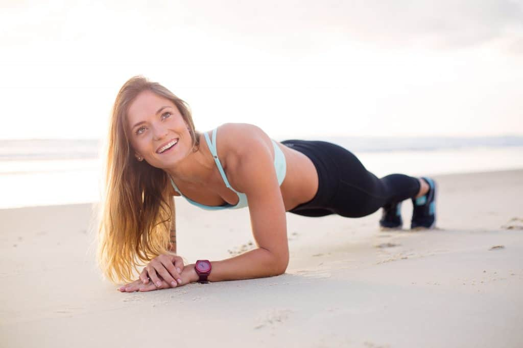 Blonde woman wearing leggings planking at the side of the beach