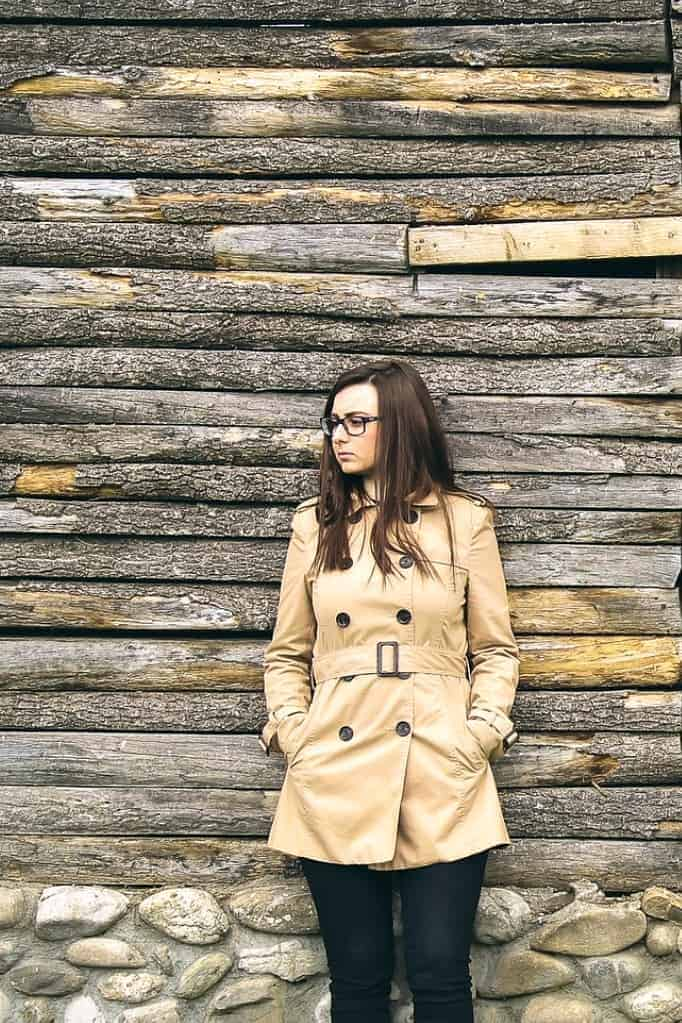 Girl with glasses wearing a duffle coat posing on a wood wall backdrop