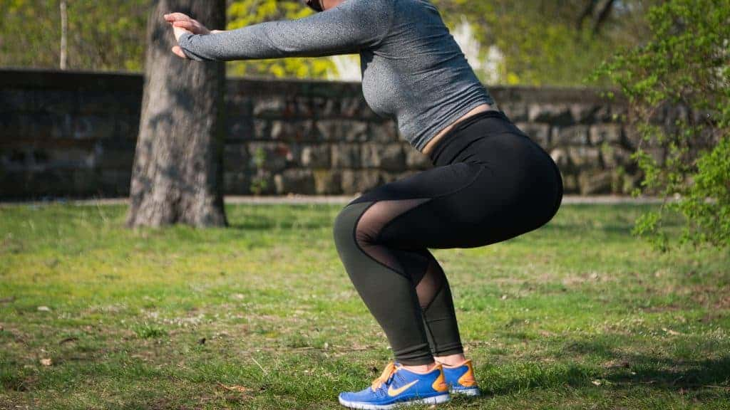 Woman doing sit-ups wearing a black leggings and blue Nike shoes.