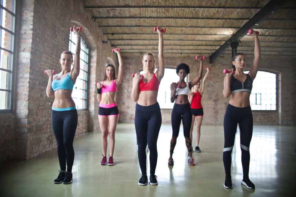Women at the gym with dumbbells while wearing leggings