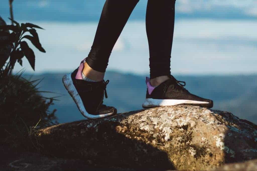 Girl wearing leggings with sneakers and standing on a rock