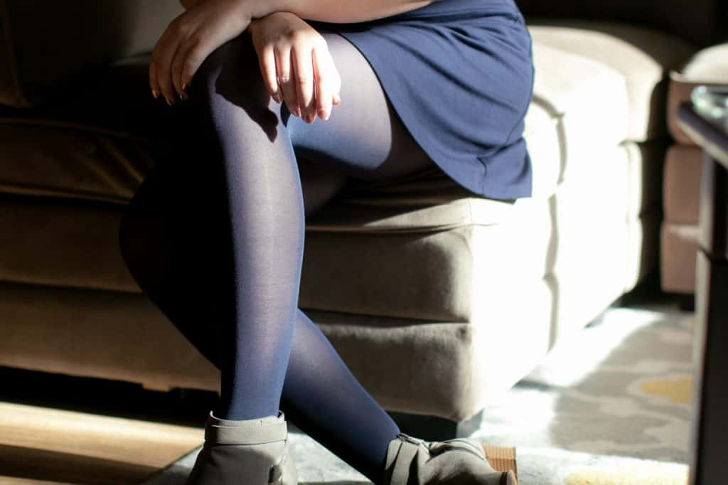 A woman wearing tights sitting on a couch