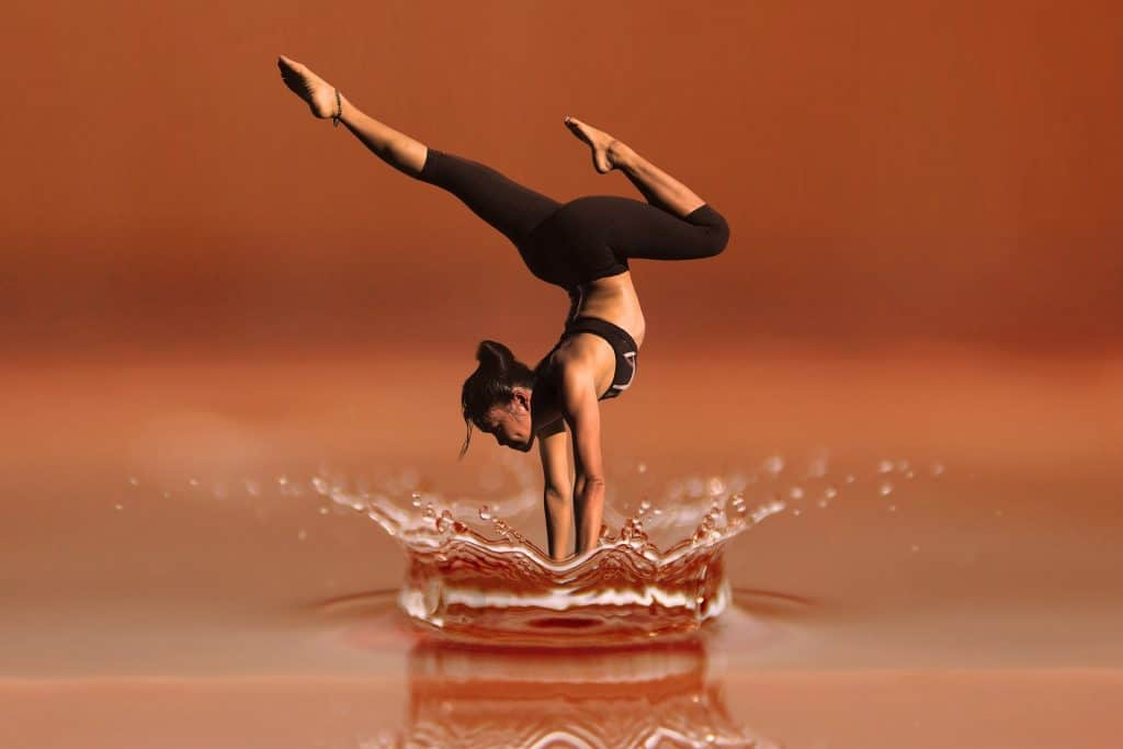 Woman doing yoga poses in water displaying what is a good GSM for leggings