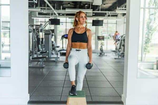 Woman wearing a black minimizer sports bra and gray colored sweatpants while holding dumbbells
