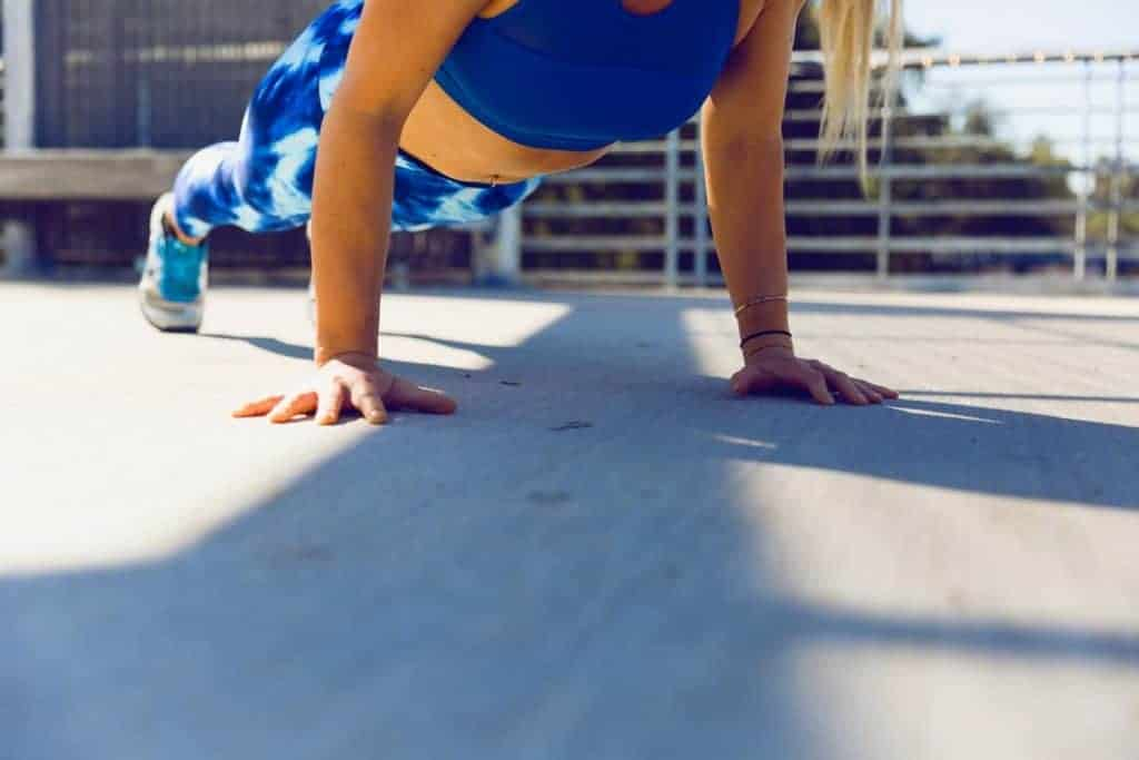 Woman doing push ups while wearing a black sports bra and printed leggings