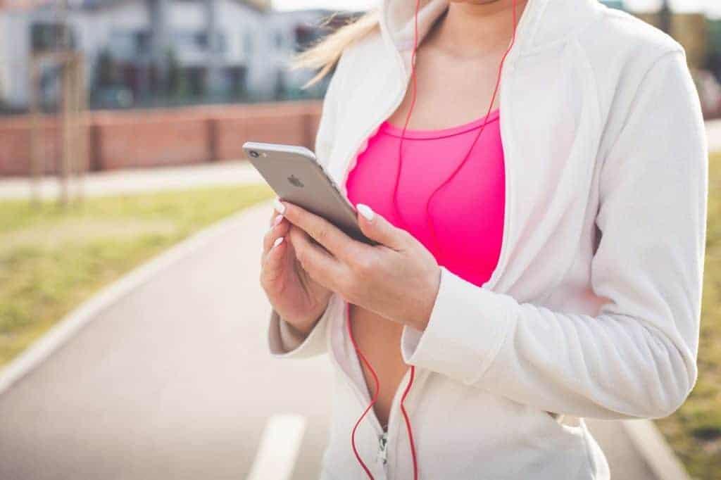 Woman wearing pink minimizer sports bra with white jacket