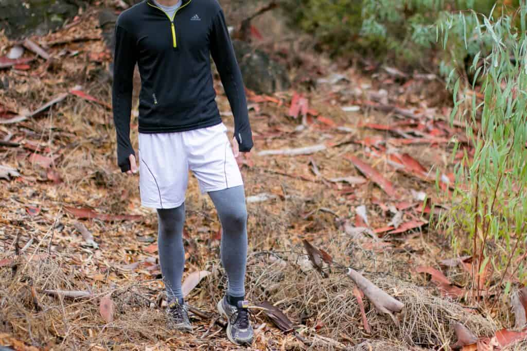 A man wearing a pair of gray leggings walking in the woods