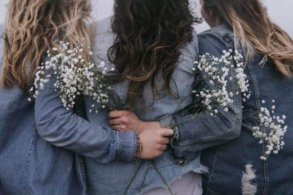 Backview of three women wearing denim jackets while holding white filler flowers