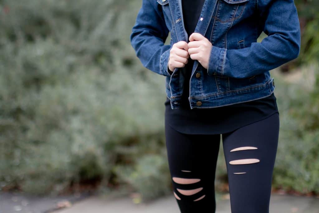 A woman wearing a denim jacket and plain black leggings
