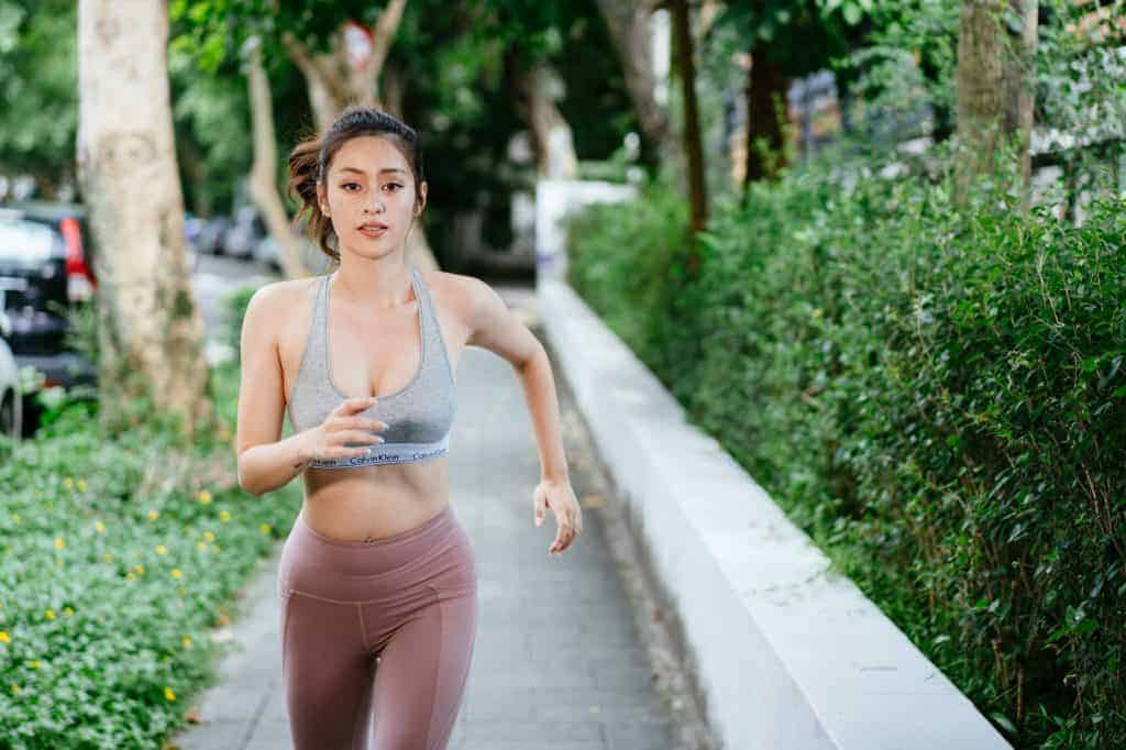 A woman in workout clothing jogging on the sidewalk