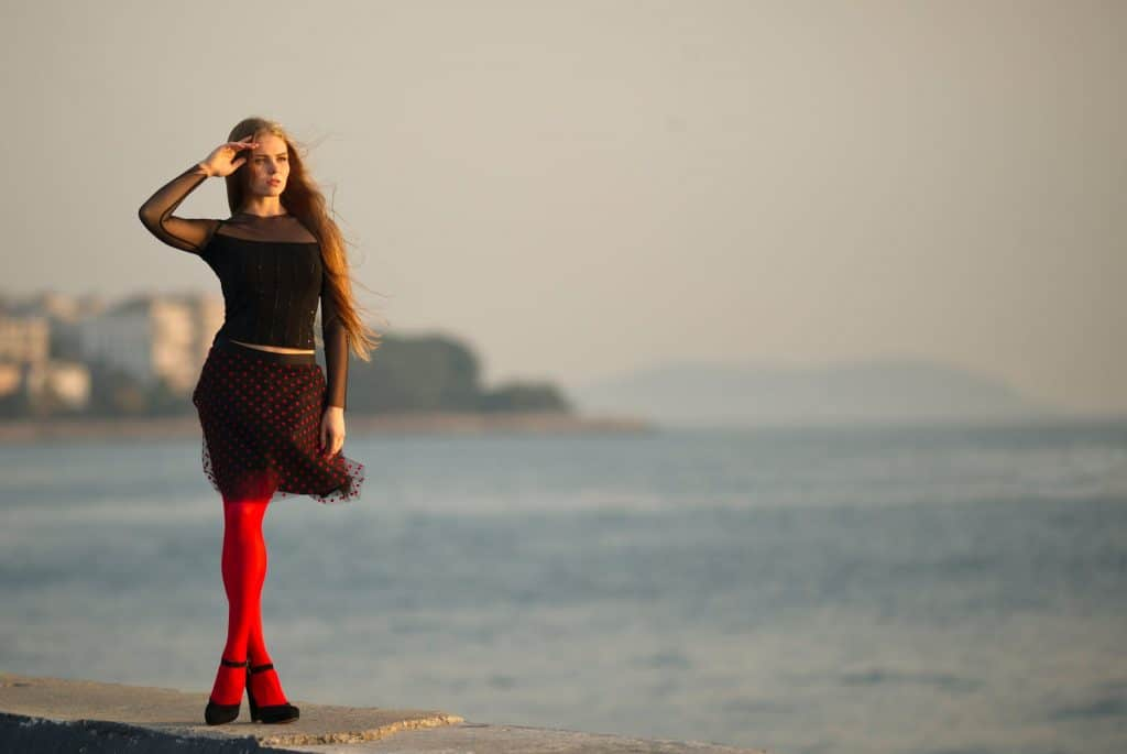 A woman wearing red leggings staring at the sea
