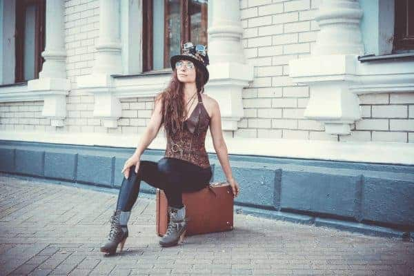 Woman wearing leather leggings with a leather top and a bucket hat