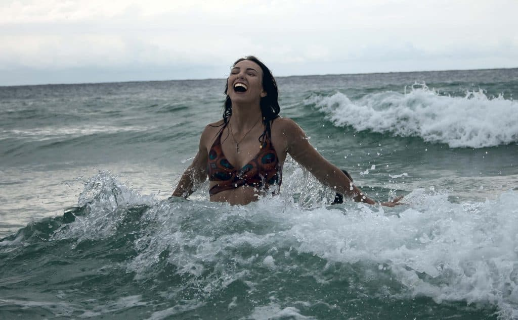 Woman getting hit by a light wave while swimming in a beach