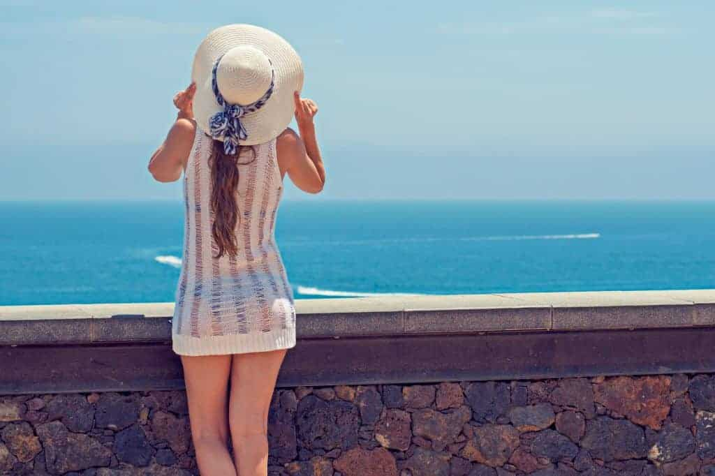 A woman wearing a sun hat facing the beach