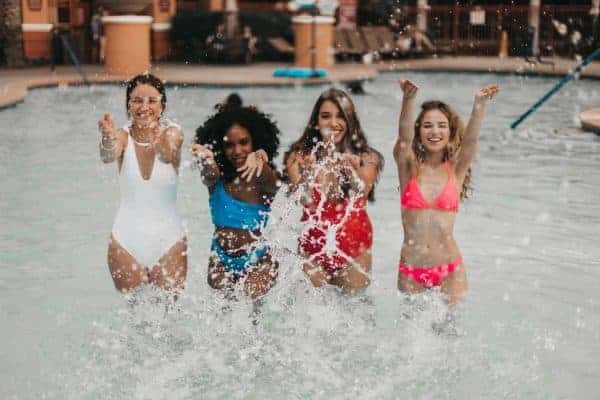 Four women splashing water in the pool