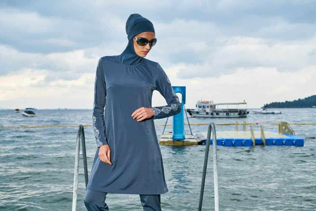 Woman wearing a blue-colored burkini swimsuit