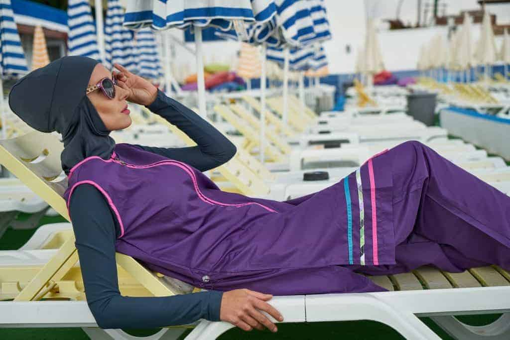 Woman in a burkini lying on pool lounge