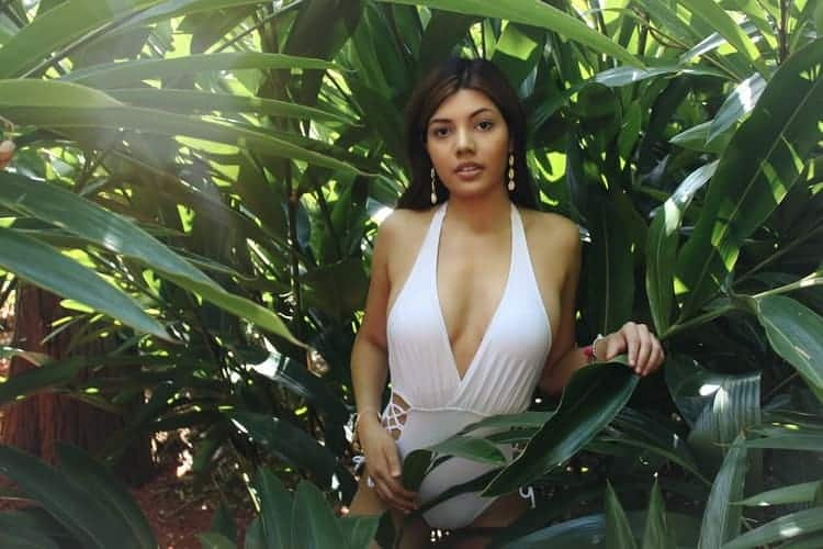 Woman wearing a white monokini while being surrounded by plants