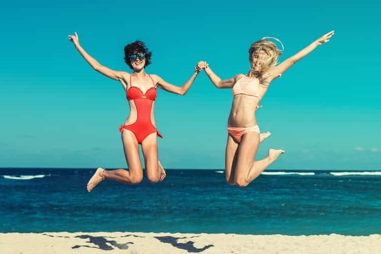 Two women jumping wearing two kinds of swimsuits