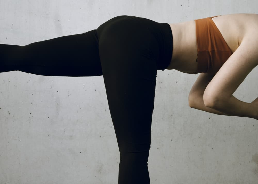 Woman in black leggings doing a yoga pose