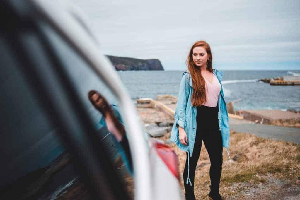 Woman in black leggings standing beside a vehicle