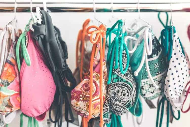 Various kinds of swimsuits hanging in a rail