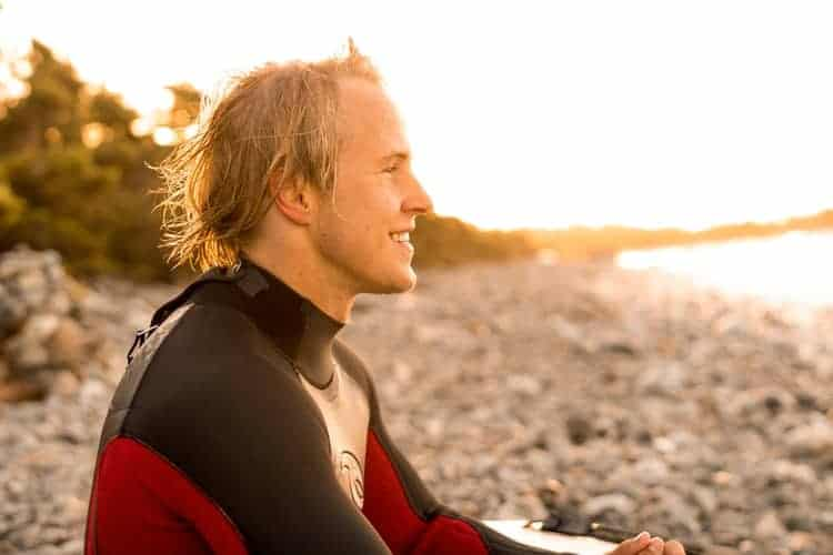 Man wearing a wetsuit while sitting in a beach
