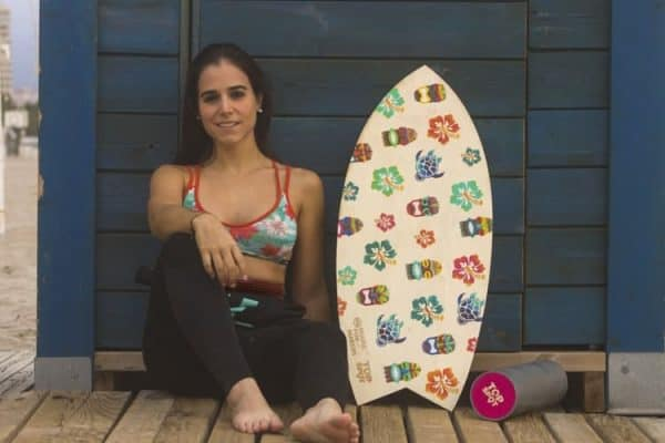 Woman sitting down while her wetsuit is only half worn showing off her bikini top