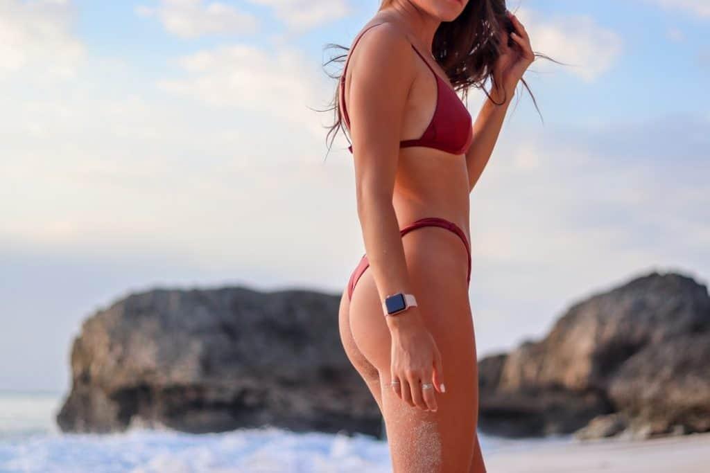 Woman in bikini standing on seashore during daytime