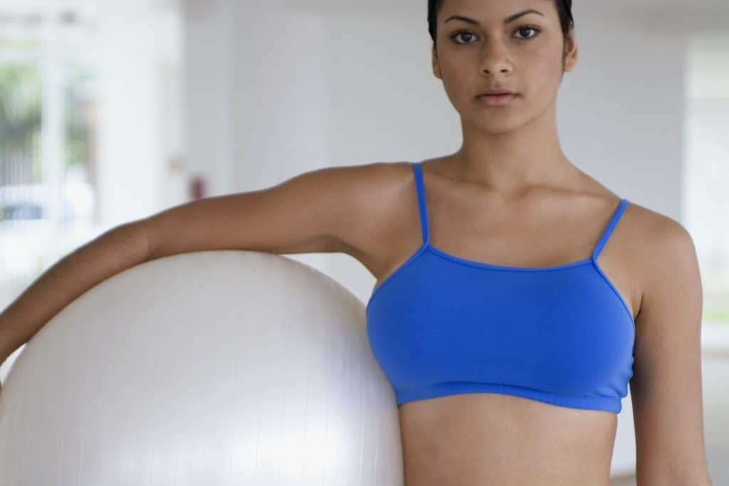 Woman wearing a blue bralette while holding a white fitness ball