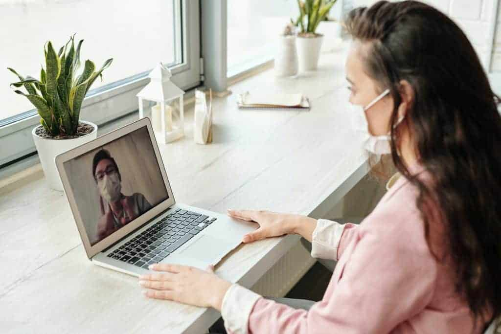 Woman wearing a pink shirt dress and white medical mask while on a video call