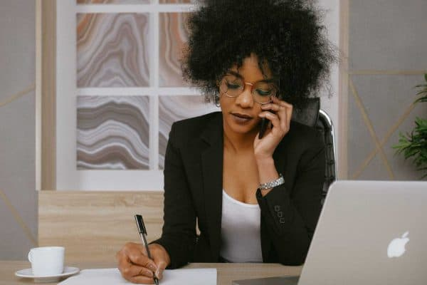 Woman wearing a black blazer and white tank top taking a call while writing down on a piece of paper