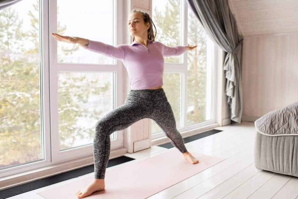 Woman wearing a long sleeve pink active-wear top and gray leggings while doing a yoga pose