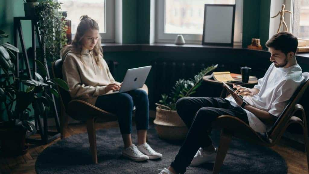 A man and a woman on their electronic devices at home while wearing indoor footwear