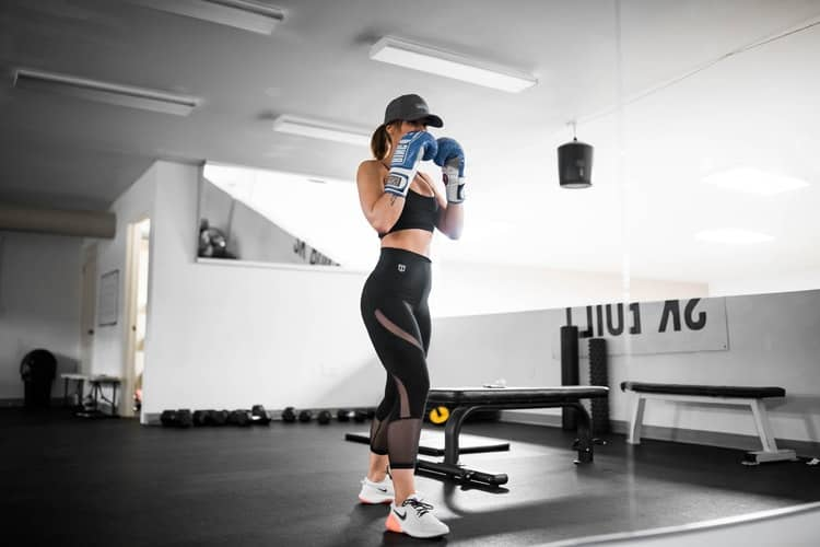 Woman wearing 7/8 leggings while doing boxing at the gym