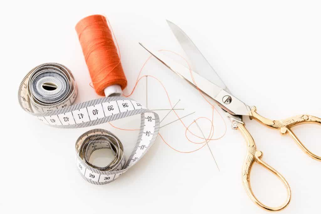 Measuring tape, thread, scissors and needles in a table