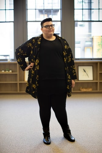 Woman wearing printed jacket over black shirt and leggings