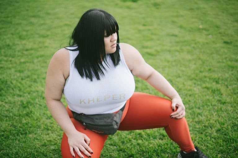 Plus size woman showing off how to wear her orange leggings in a park